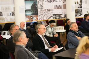 Udeleženke in udeleženci, v ozadju razstavljeni nagrajene rešitve z natečaja za spomenik žrtvam vseh vojn
